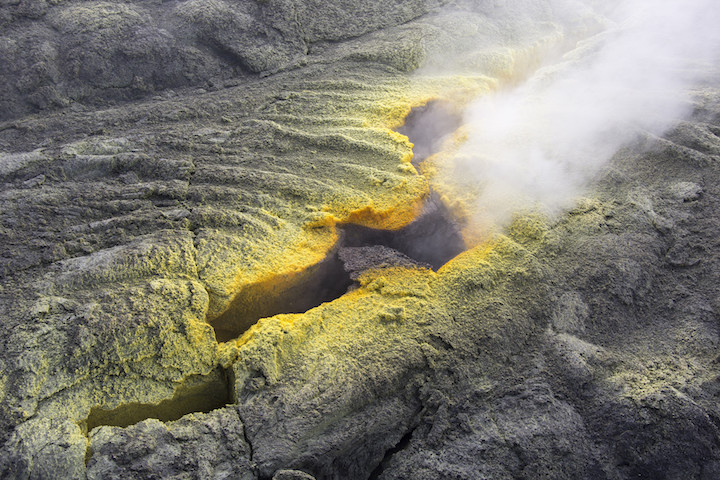 A fumarole at Puʻu ʻŌʻō Crater. Hawaii. The yellow crust along the margin of the fumarole is made of sulphur crystals. The crystals form when sulphur vapour cools as it is released from the fumarole. Source: U. S. Geological Survey (2016) Public Domain
